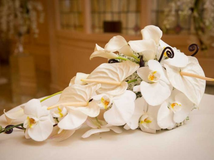 bridal bouquet made of Phalaenopsis orchids, calla lilies, anthorium, and gypsophila.